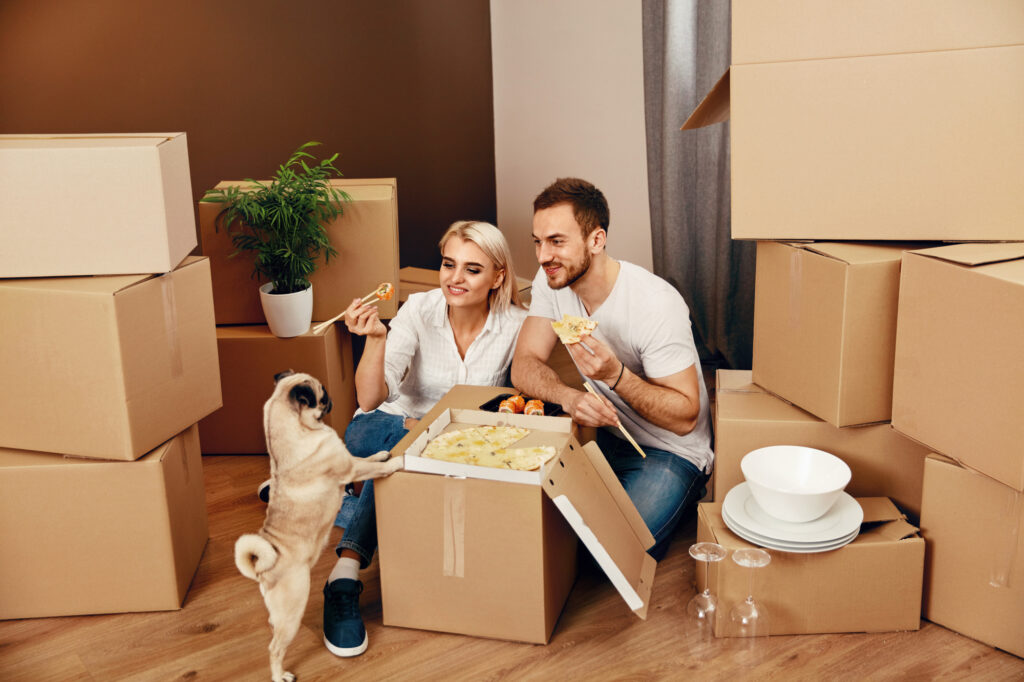 Man and woman eating with dog on moving box.